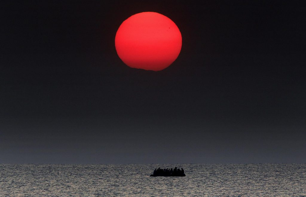As the sun rises a dinghy overcrowded with Syrian refugees drifts in the Aegean sea between Turkey and Greece after its motor broke down while traveling from the Turkish coast to the Greek island of Kos, August 11, 2015. A Greek coast guard responded to distress signals and arrived at the scene to help.