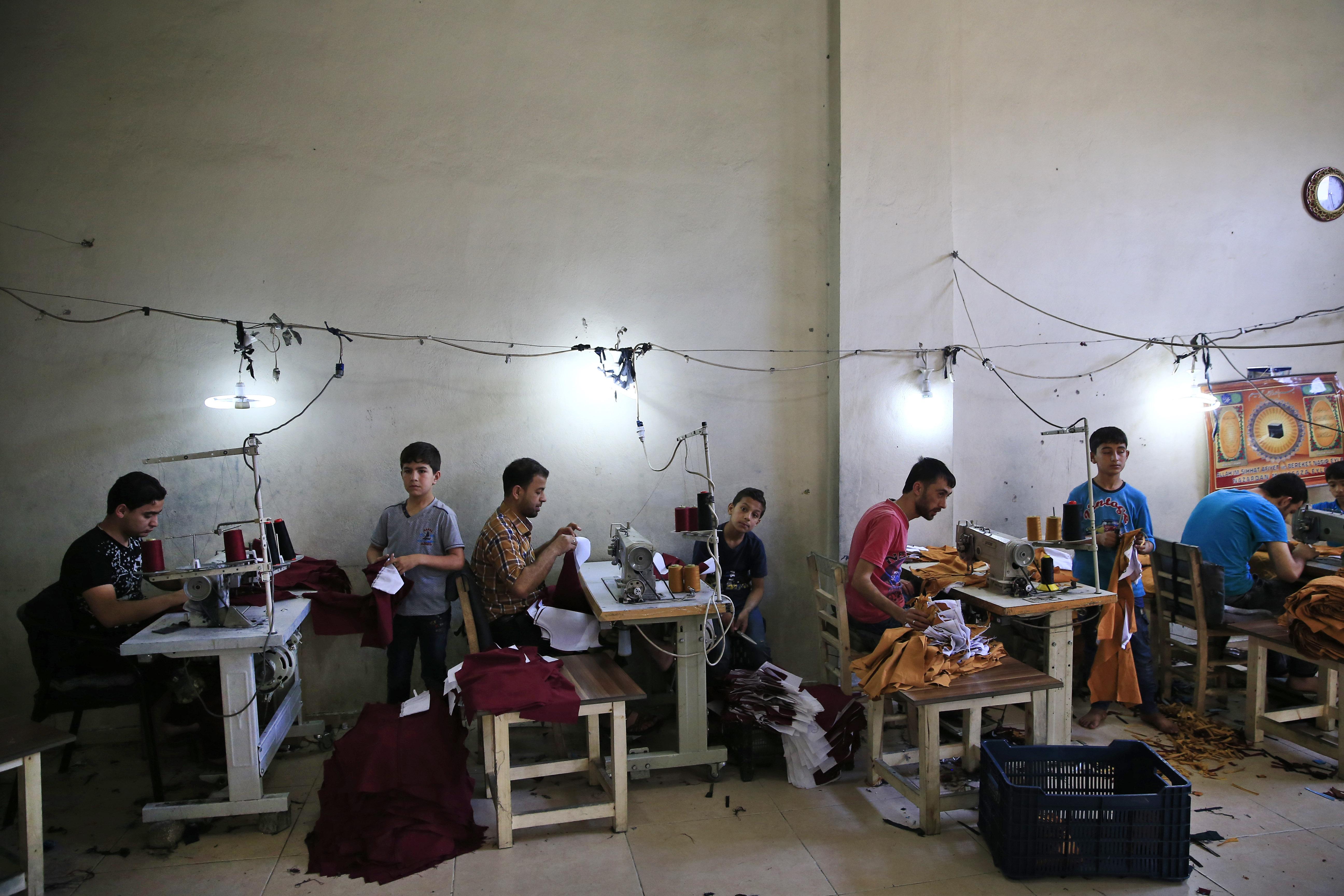 Σύροι πρόσφυγες, ανάμεσά τους και παιδιά, δουλεύουν σε βιοτεχνία ενδυμάτων στο Gaziantep, ΝΑ Τουρκία, © Λευτέρης Πιταράκης/Associated Press