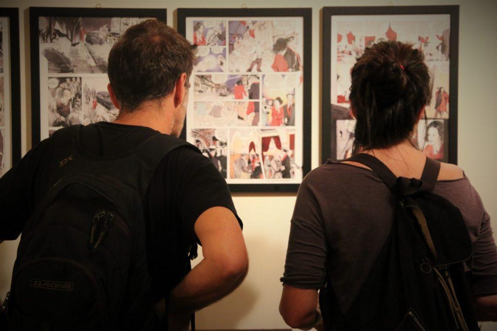 Επισκέπτες της έκθεσης διαβάζουν το κόμικ του Γιώργου Φαραζή ©Δανάη Κωτσάκη