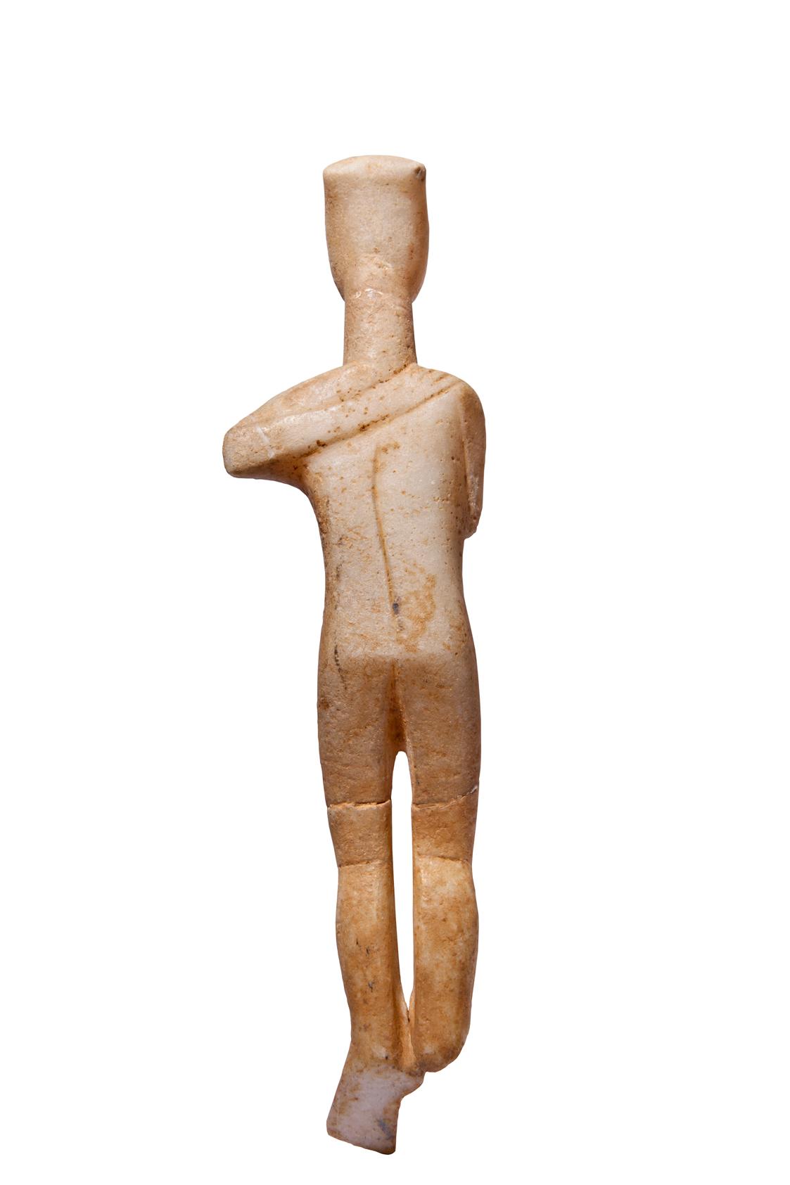 Μαρμάρινο γυναικείο ειδώλιο από σύμπλεγμα μορφών. Το χέρι στην πλάτη ανήκε σε άλλη μορφή, η οποία εναγκαλιζόταν τη σωζόμενη. Έπειτα από ατύχημα το σημείο θραύσης εξομαλύνθηκε και η θέση του χεριού αποδόθηκε εντελώς αφύσικα. (περ. 2700-2400/2300 π.Χ.) Αθήνα, Μουσείο Κυκλαδικής Τέχνης, ΝΓ 330. Photo © Μουσείο Κυκλαδικής Τέχνης/Ειρ. Μίαρη