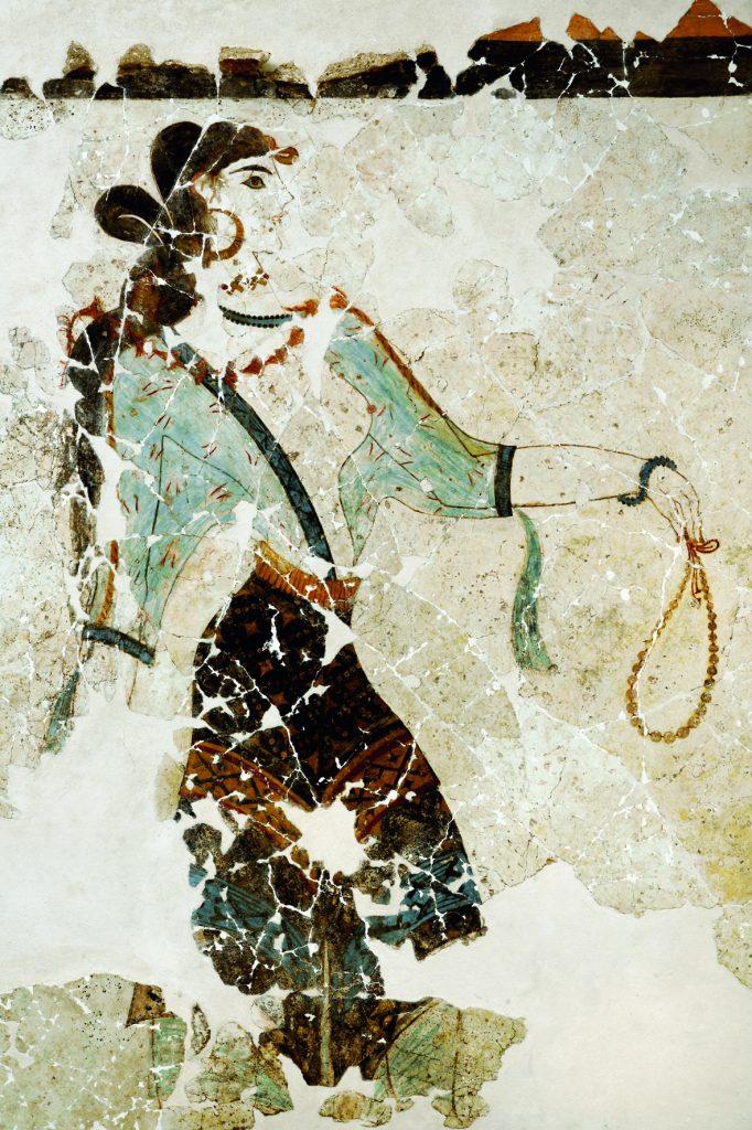 Η εικονιζόμενη «Λατρεύτρια», ώριμη γυναίκα, φοράει αραχνοΰφαντο διαφανές περικόρμιο και προτείνει το αριστερό της χέρι κρατώντας πολύτιμο περιδέραιο.