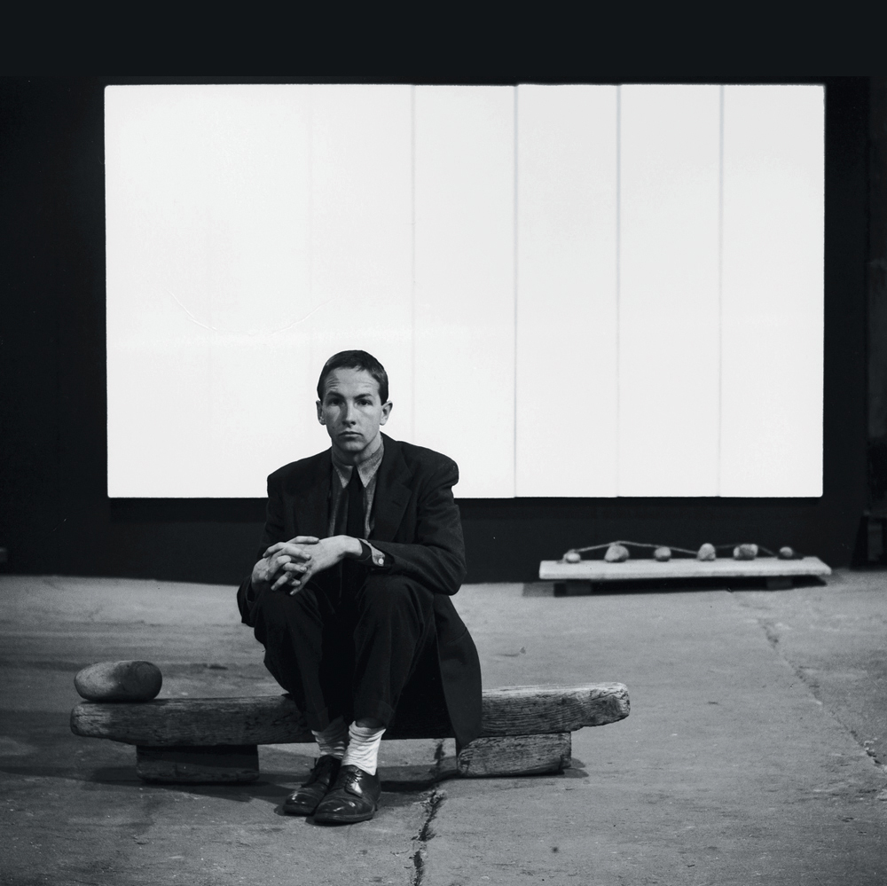 Photograph of Robert Rauschenberg seated on Untitled (Elemental Sculpture) with White Painting (seven panel) behind him at the basement of Stable Gallery, New York (1953). © Photograph: Allan Grant, Life Magazine © Time Warner Inc/Robert Rauschenberg/VAGA, New York and DACS, London 2006