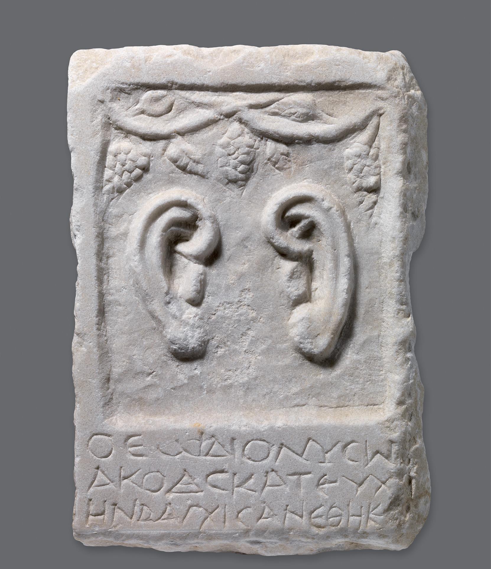 Μαρμάρινο ενεπίγραφο ανάγλυφο με παράσταση αυτιών 2ος αι. μ.Χ. Ύψ. 29 εκ.· Πλ. 20 εκ. Θεσσαλονίκη, Σαραπείον Θεσσαλονίκη, Αρχαιολογικό Μουσείο