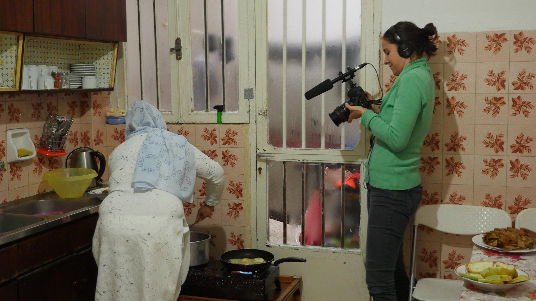 καλλιτέχνιδα Jana Koelmel εν δράσει, ενώ καταγράφει στιγμές από τη ζωή μιας Αφγανής μετανάστριας στην κατοικία της στην Αθήνα.