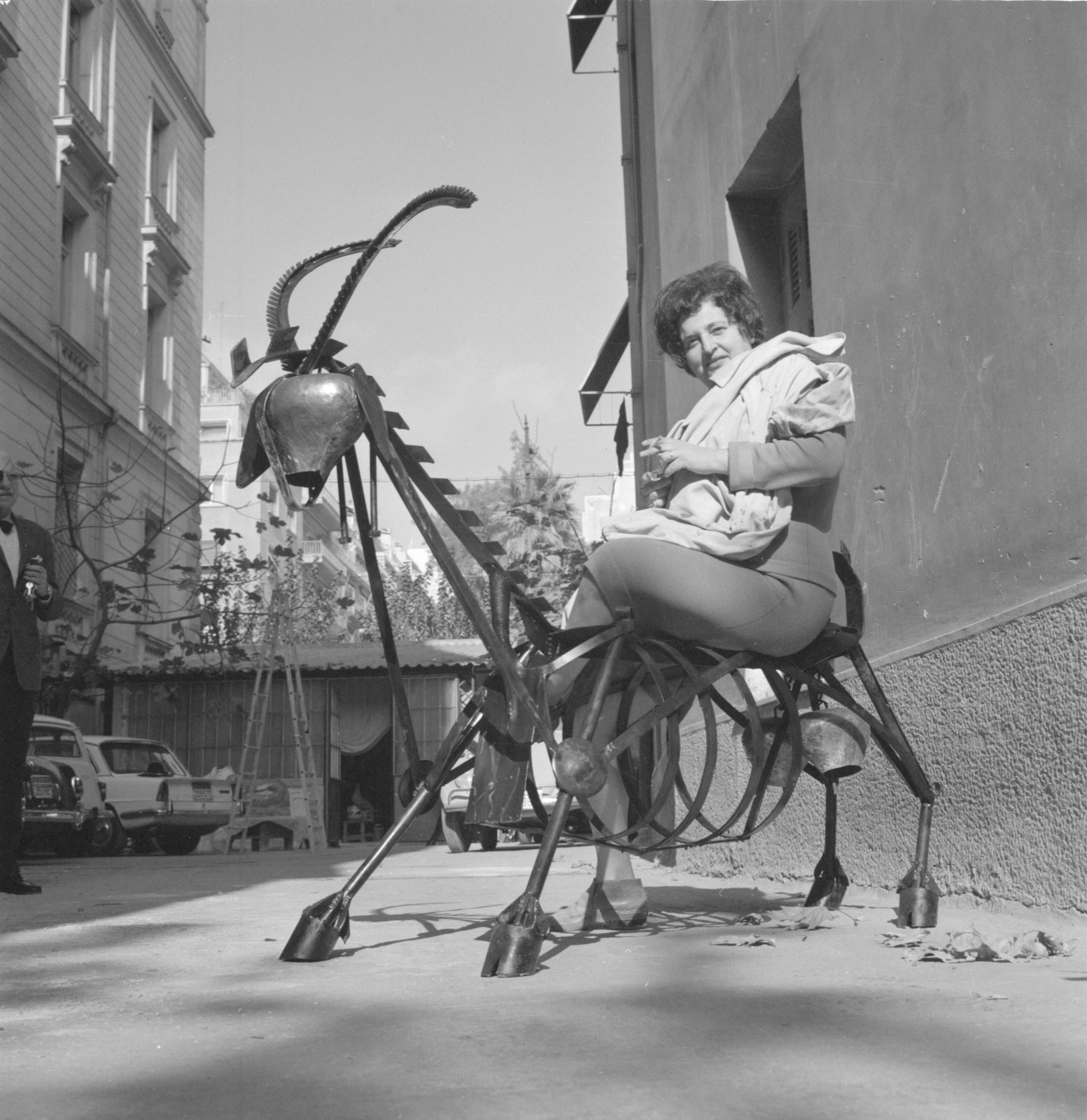 Η Ναταλία Μελά ποζάρει πάνω στο έργο της (κατσίκα) στην αυλή του εργαστηρίου της στην οδό Μουρούζη, Αθήνα, δεκαετία 1960