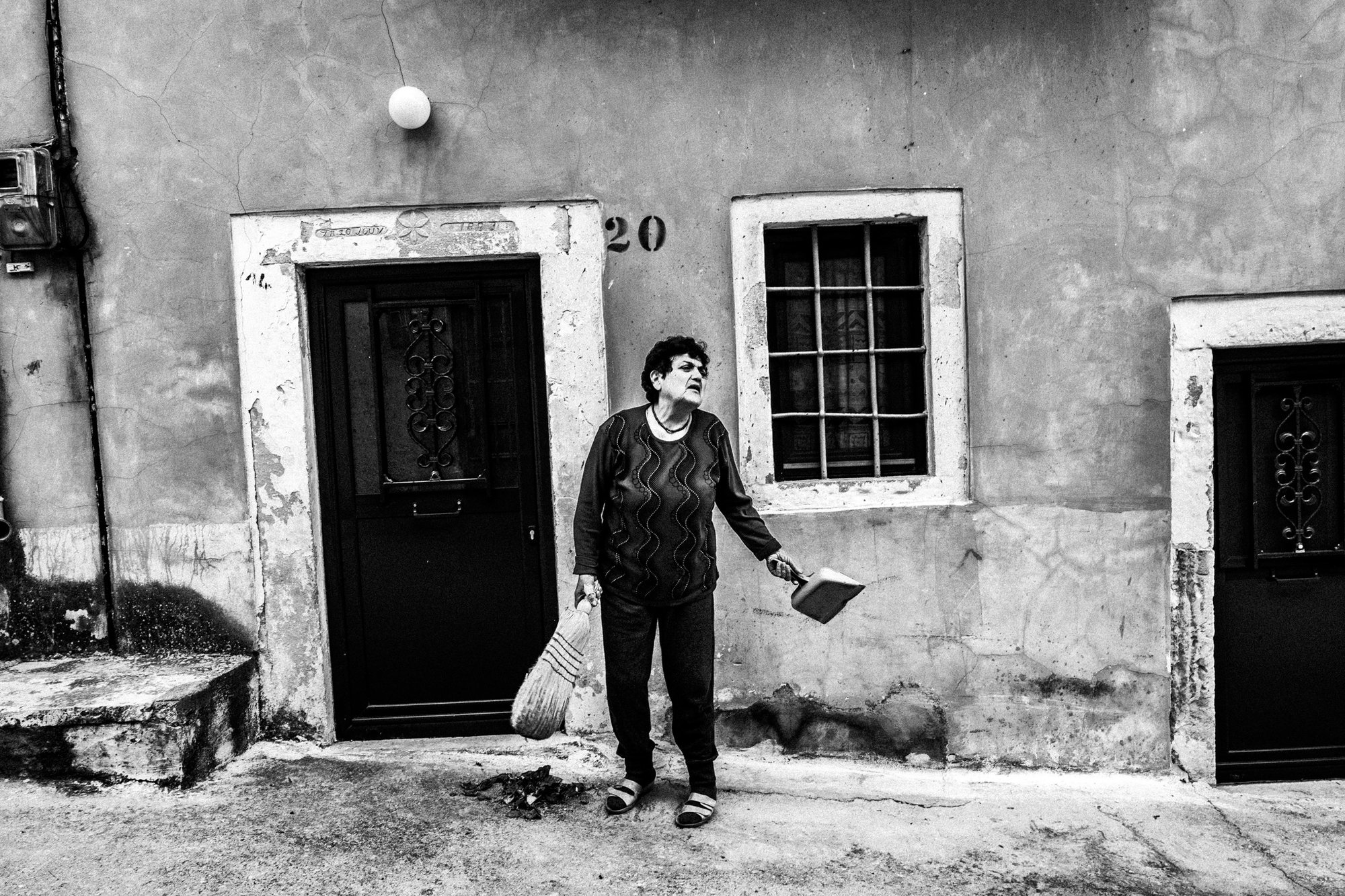 Woman sweeping her front porch at Patrika village Ελλάδα. Βόρειο Αιγαίο. Chios. © George Tatakis