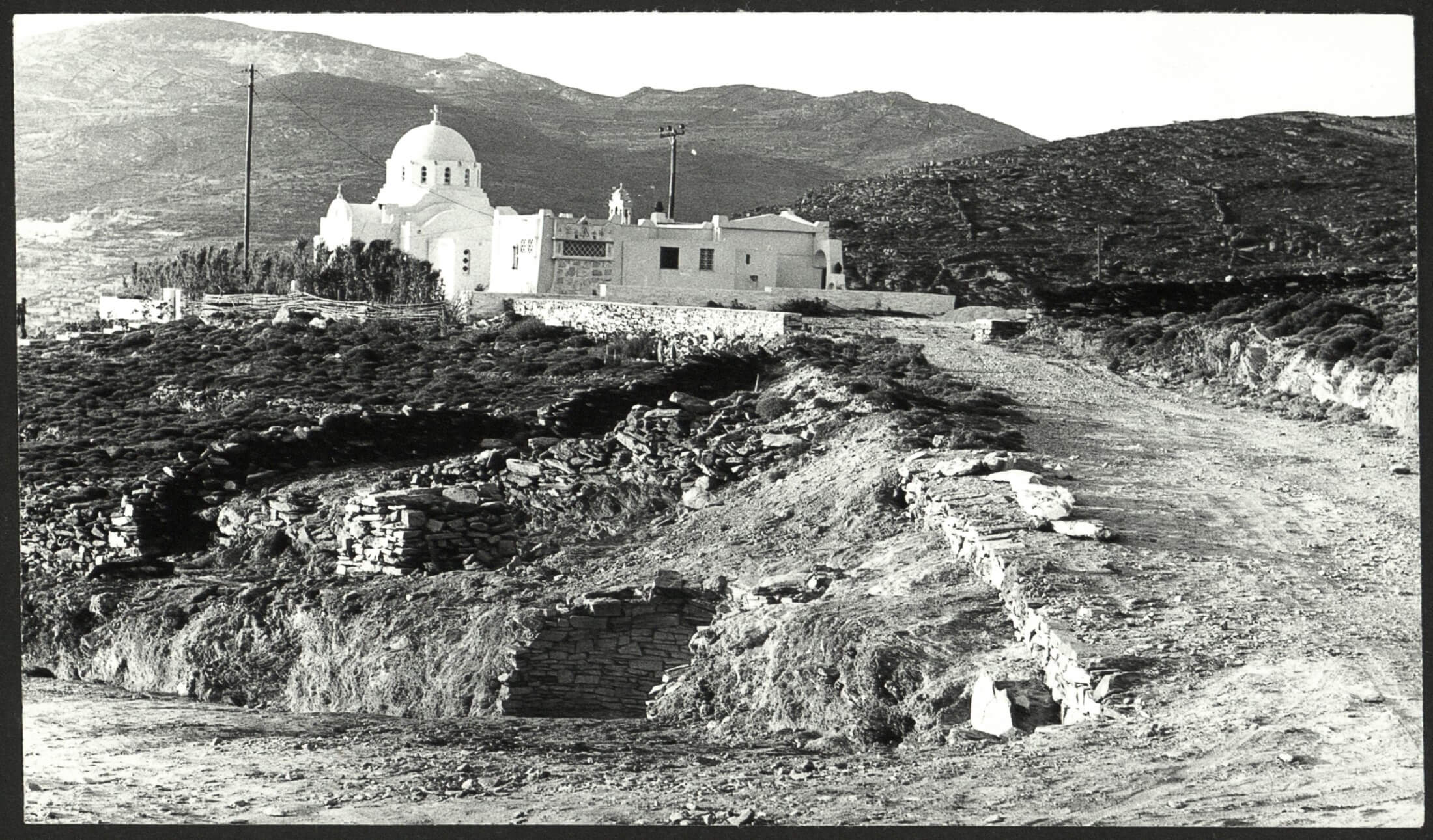 Άποψη της ανασκαφής στην Αγία Θέκλα, στην Τήνο, το 1979. Διακρίνονται τα υπολείμματα του θολωτού τάφου (κάτω) και η ομώνυμη εκκλησία (πάνω). © Αρχείο της εν Αθήναις Αρχαιολογικής Εταιρείας